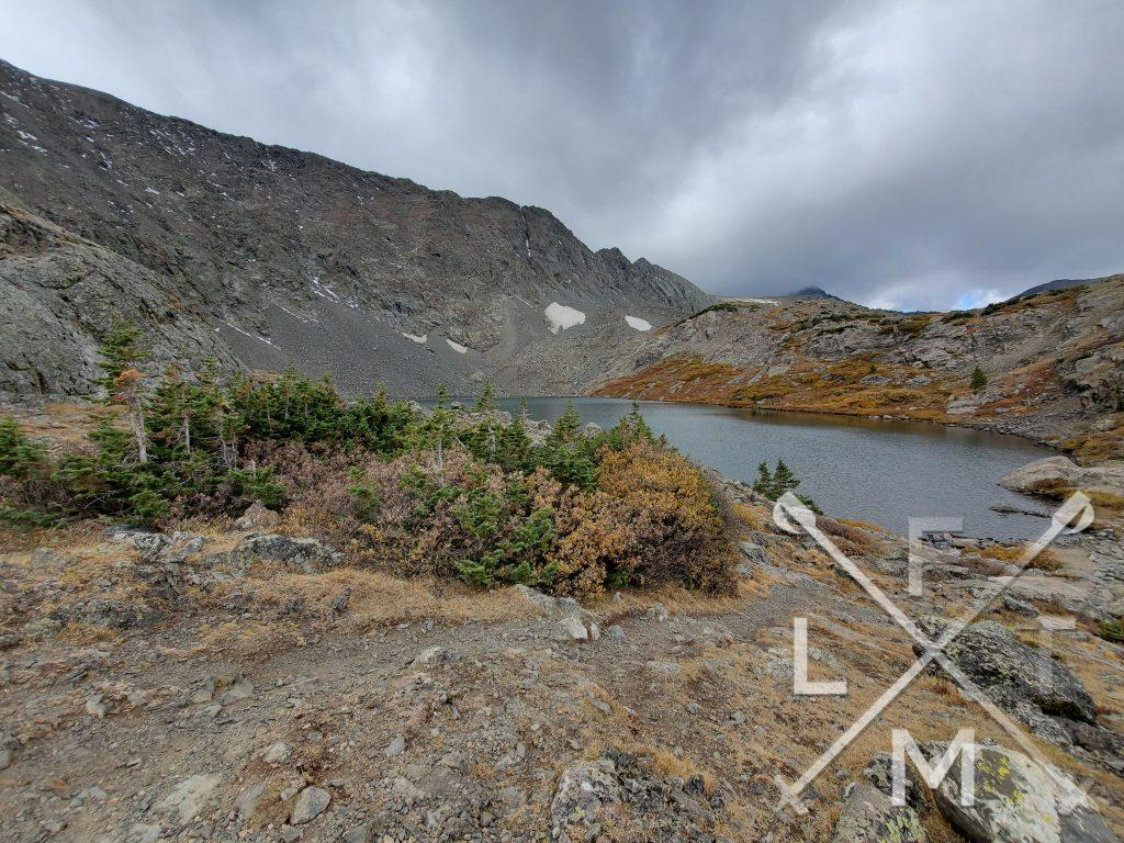 The Storms of the Hiking Seasons depicted by gray storm clouds over a mountain lake.