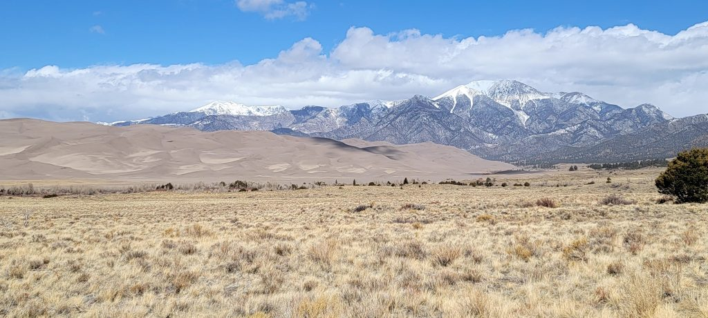 The view of the dunes and mountains from the entry road of Great Sand Dunes National Park.  The sandy dunes sit as almost a small model of the dark rocky and snow capped mountains behind them.