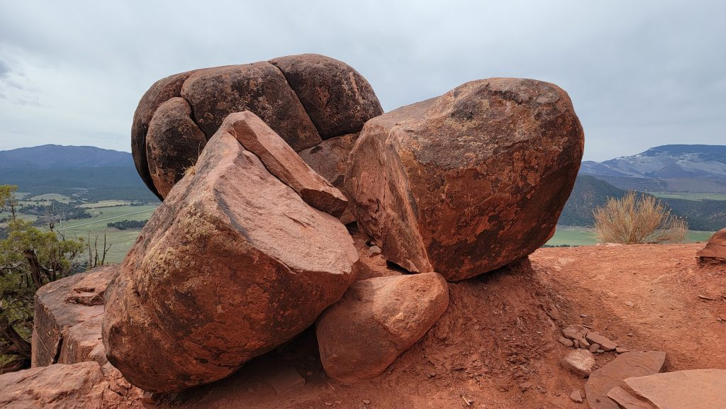 Some giant boulders sitting on the edge of the trail on the Mushroom Rock hike.  The boulders are a red tint to match the red dirt trail below.