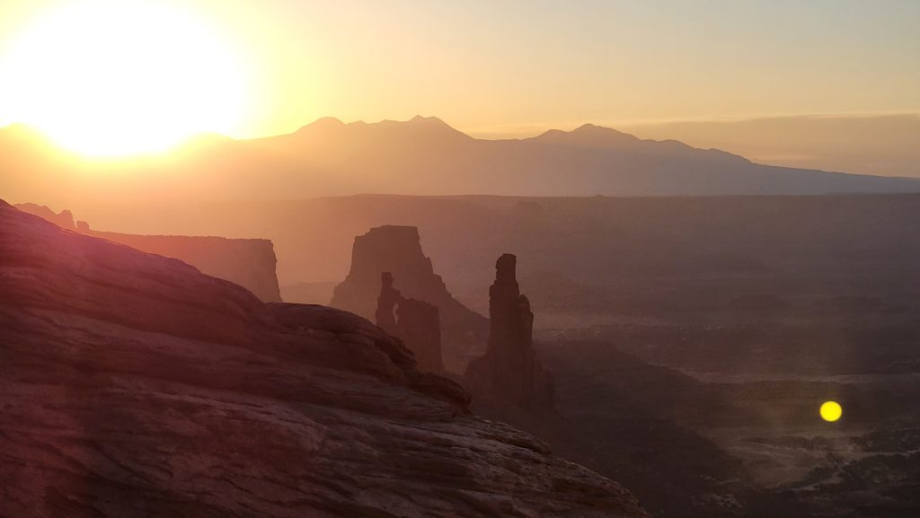 While watching sunrise at Mesa Arch the view from the side of the arch shows the large bulb of the sun just over the mountains illuminating the pillars and spires in the lower canyon below.
