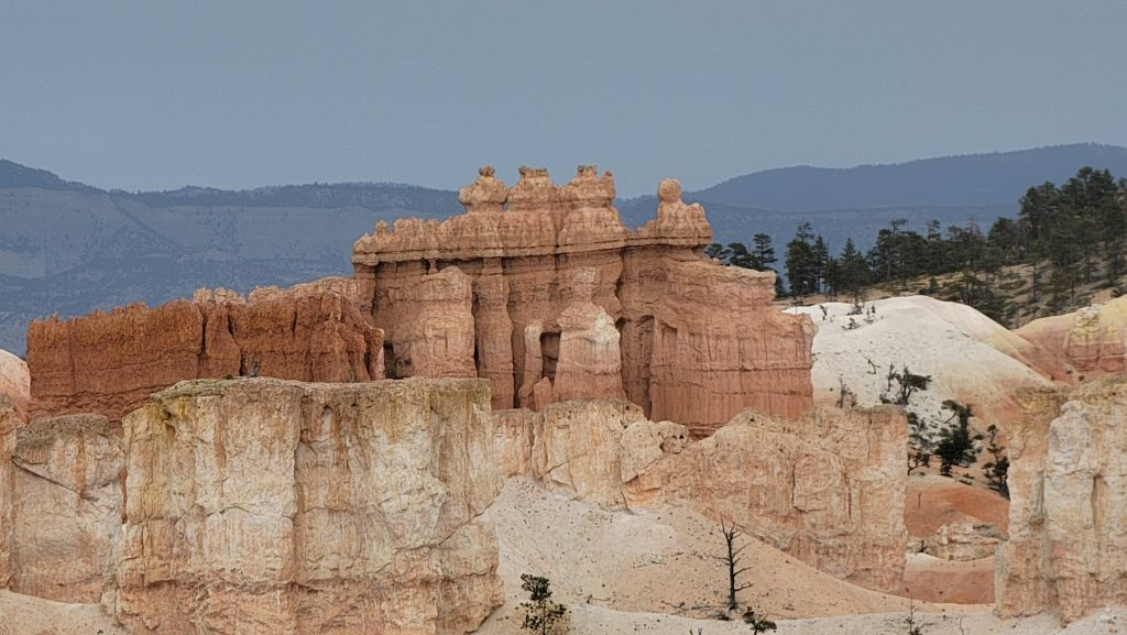 A rock formation that looks like building with round columns in the front and what look like decorative pieces on top along with a tall rock wall as part of the Queen's Garden Loop in Bryce Canyon National Park.