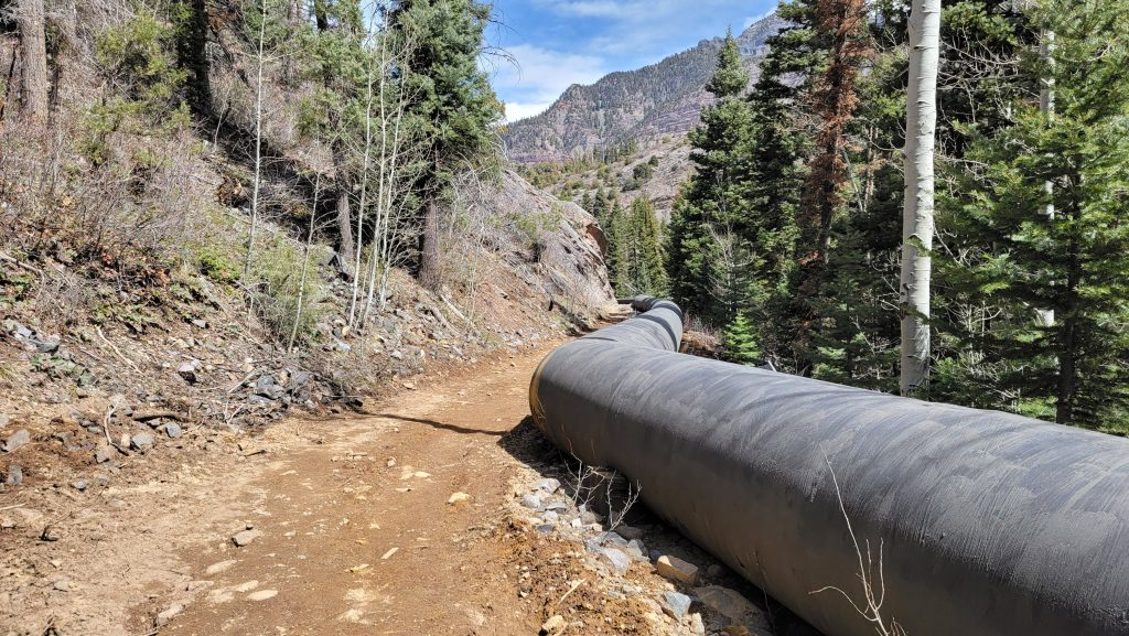 The giant water pipe runs down the right side of the frame while a service road/trail runs next to it on the Ouray Perimeter Trail.