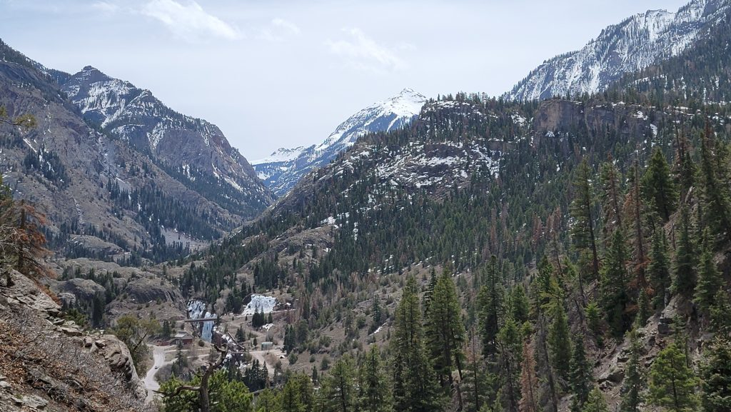 A view looking across the valley on the Ouray Perimeter trail. There are rolling hills with a snow capped peak in the distance.