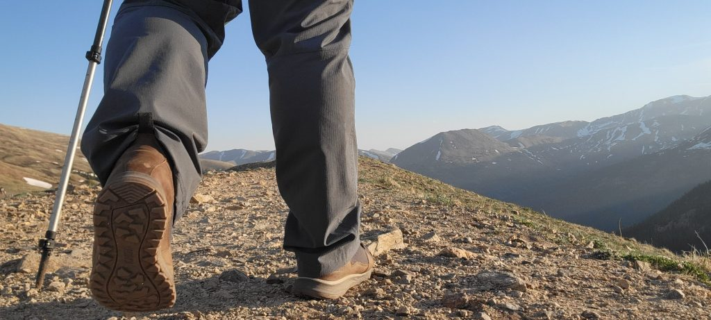 The view of my Kodiak Skogan Boots from Kodiak Boots as I traverse a Mountain pass.  You can see the tread of my boot in the foreground and mountain peaks in the background.