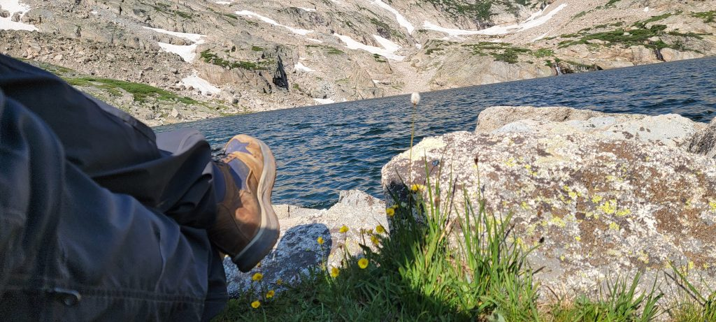 The Skogan Hiking boots from Kodiak Boots resting next to a mountain lake.  The boots have good waterproofing that even take being submerged.