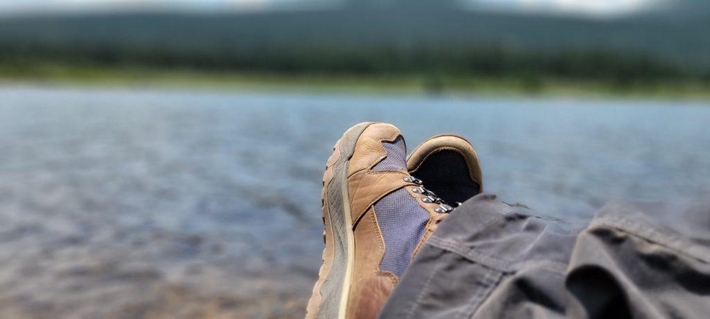 My feet crossed at the edge of an alpine lake. I am wearing the Kodiak Skogan Hiking boots from Kodiak Boots.