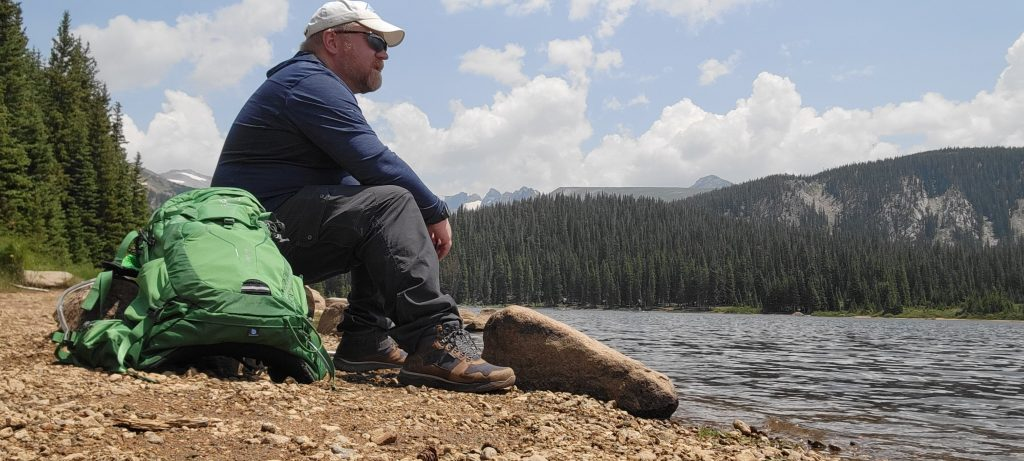 My sitting next to an alpine lake taking in the views.  I am wearing Kodiak Skogan Hiking Boots from Kodiak Boots, a Kuhl Engineered Hoodie, Kulh Renegade Cargo pants, and an Osprey Manta backpack.
